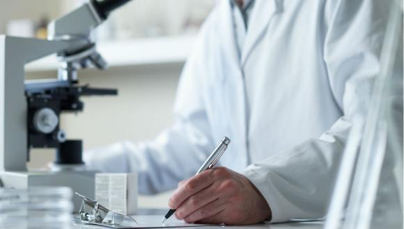 person working in a lab with microscope and pen