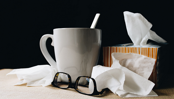 white ceramic mug on white table beside black eyeglasses and box of tissues